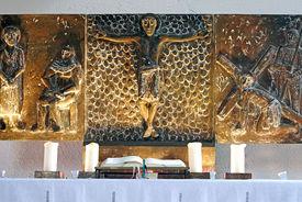 Bronze-Relief der Passion auf Altar, Künstler Fritz Fleer, unten 4 Kerzen neben offener Bibel, gelbe Strahler ein - Copyright: Manfred Maronde